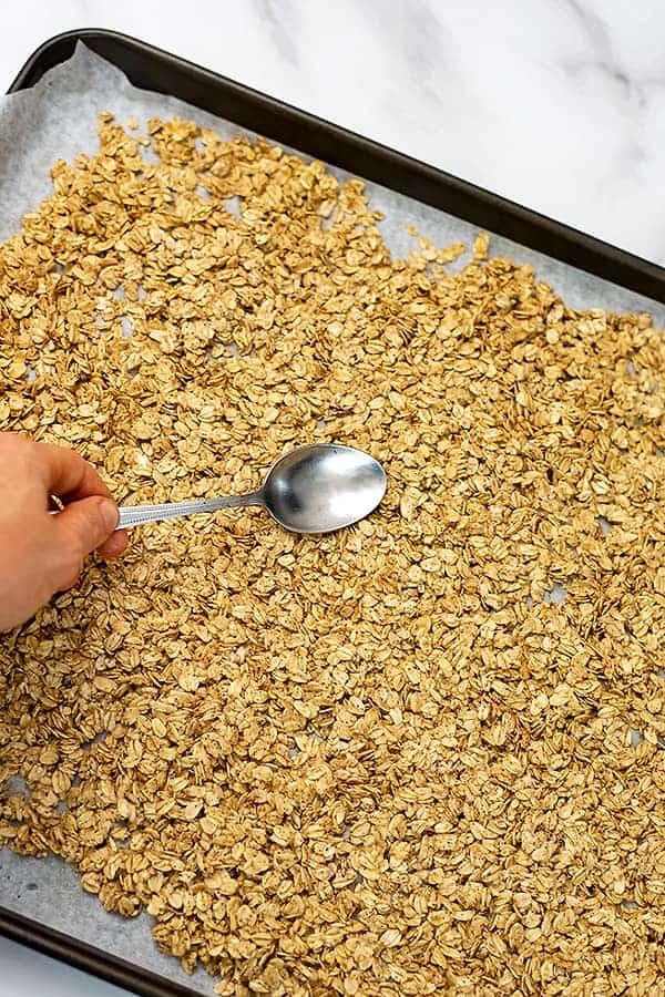 Baking sheet with raw granola being spread out with spoon.