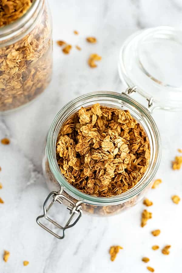 Glass container filled with vegan granola with granola around the jar.