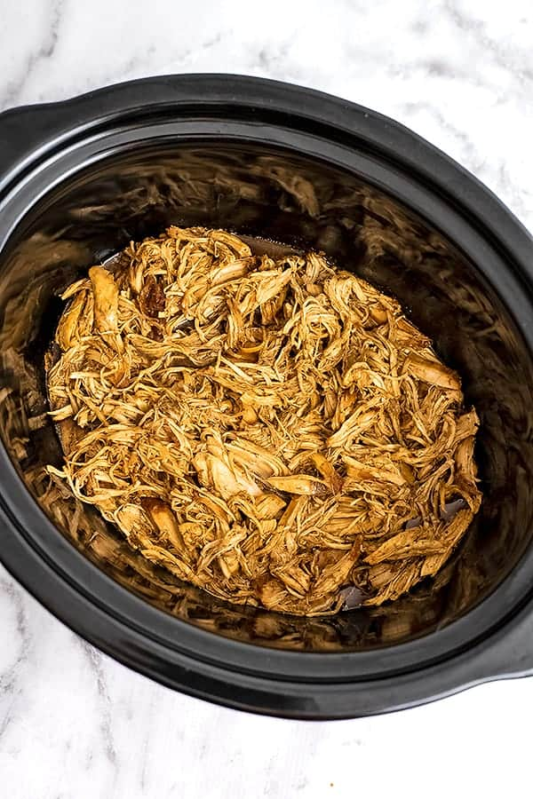 Crock pot filled with shredded balsamic chicken.