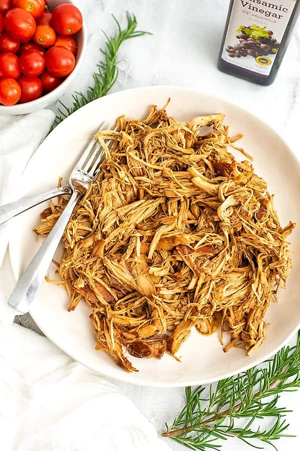 White plate filled with shredded balsamic chicken, tomatoes in background.