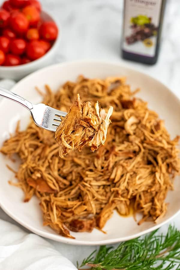 Fork holding shredded balsamic chicken over a white plate.
