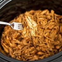 Fork holding shredded balsamic chicken over a crock pot.