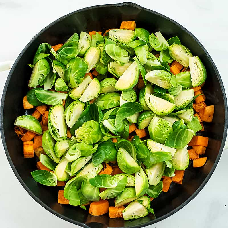 Quartered brussels sprouts over sweet potatoes in skillet.
