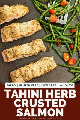 Sheet pan with tahini herb crusted salmon and green beans and tomatoes.