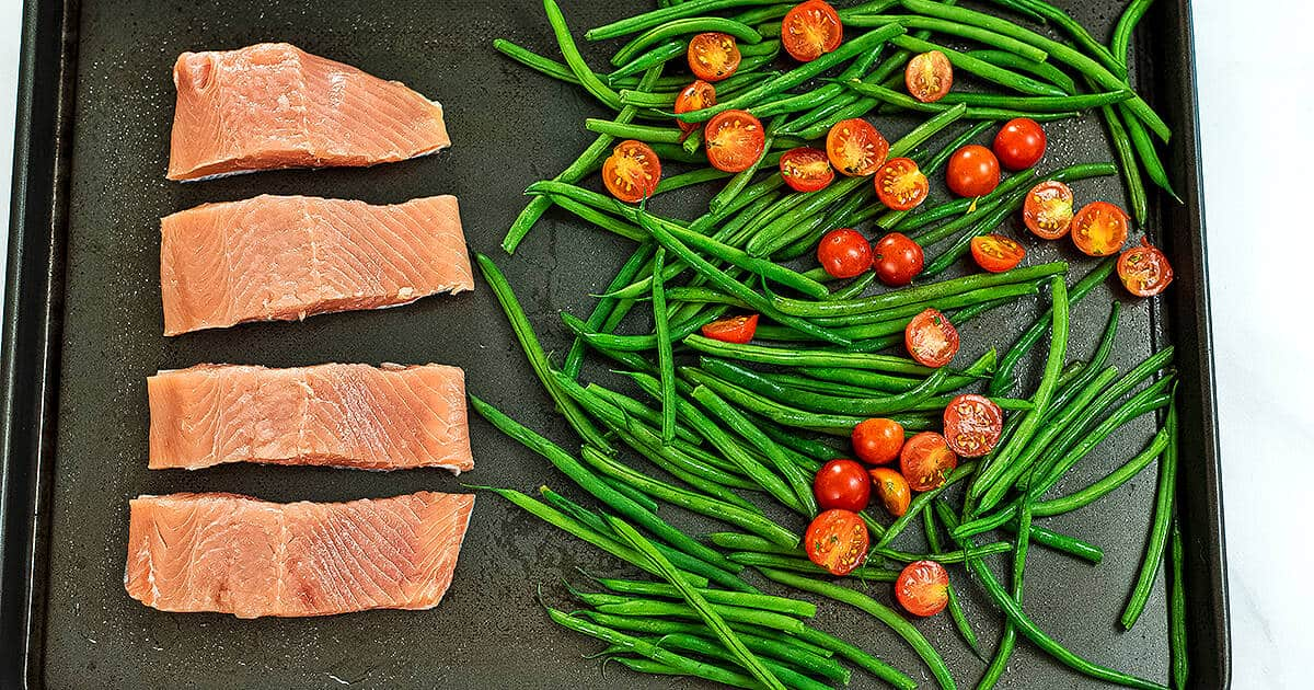 Sheet pan with salmon filets, green beans and tomatoes.