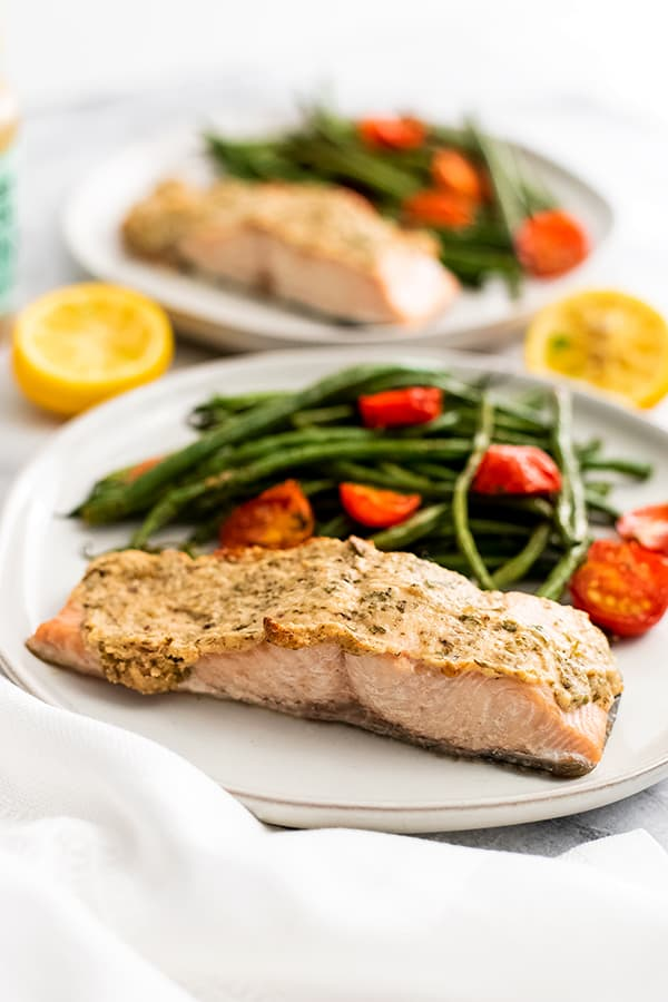 White plate filled with herb crusted salmon and vegetables.
