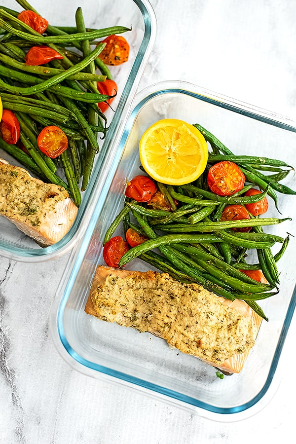 Glass container filled with tahini crusted salmon, green beans, tomatoes and a lemon.