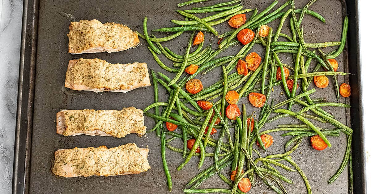 Sheet pan with cooked tahini herb crusted salmon, green beans and tomatoes.