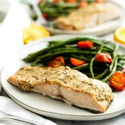 Plate filled with tahini herb crusted salmon, green beans and tomatoes.