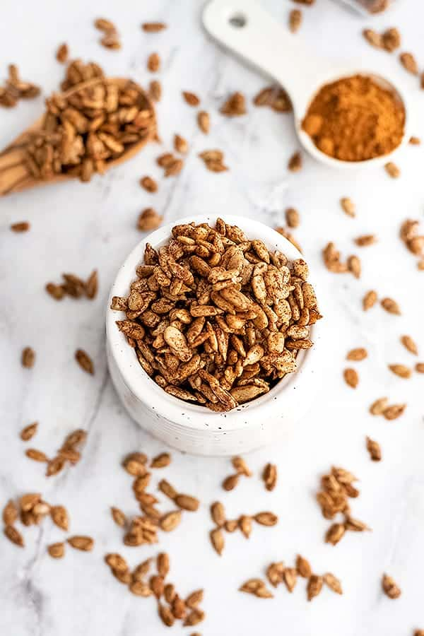 White jar filled with spiced sunflower seeds.