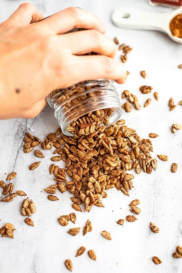 Hand pouring out a glass jar of spiced sunflower seeds.
