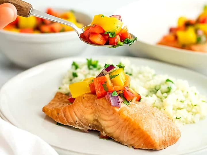 Salmon filet on a white plate with mango salsa spooning on top.