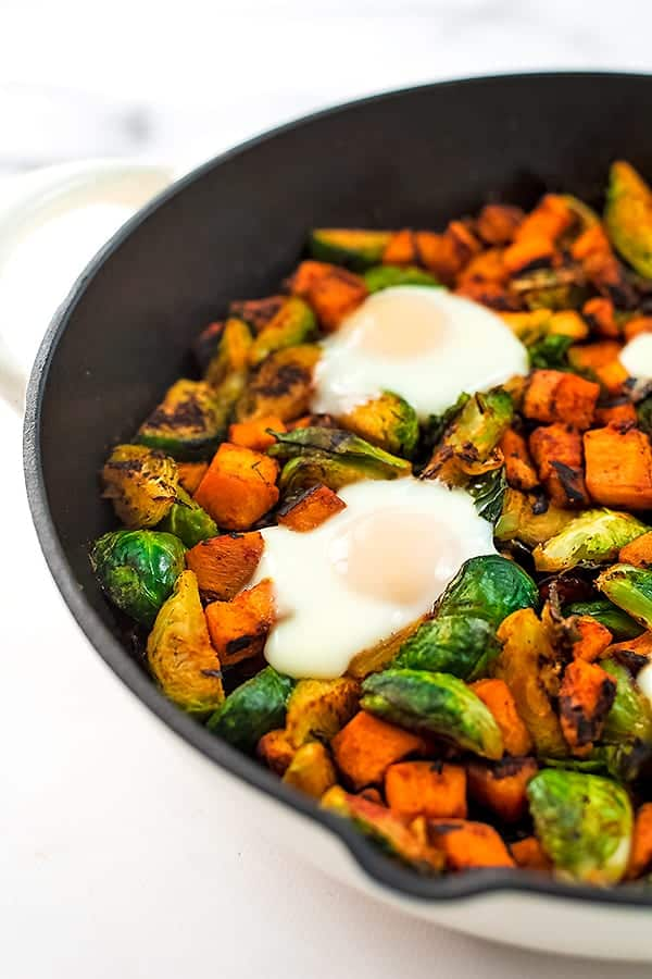 Sweet potato hash with eggs in a cast iron skillet.