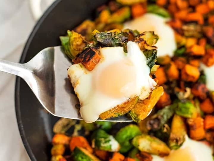 Spatula holding a serving of sweet potato hash and an egg.