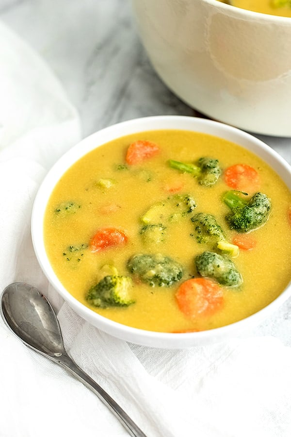 Bowl of broccoli cheese soup with a spoon to the left of the bowl.