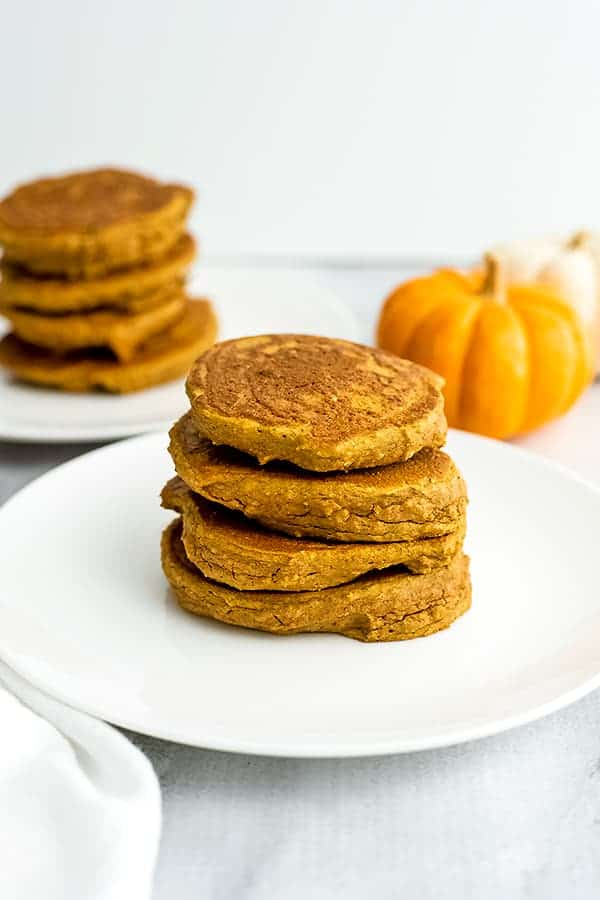 Stack of protein pumpkin pancakes on a white plate.