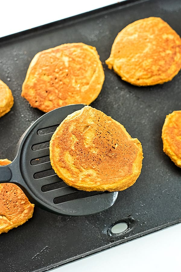 Spatula holding a pumpkin pancake after cooking over a griddle.