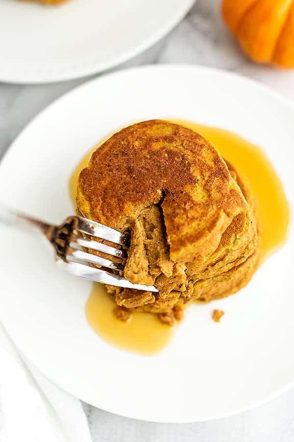Forkful of of pancake being taken from the stack of pancakes.