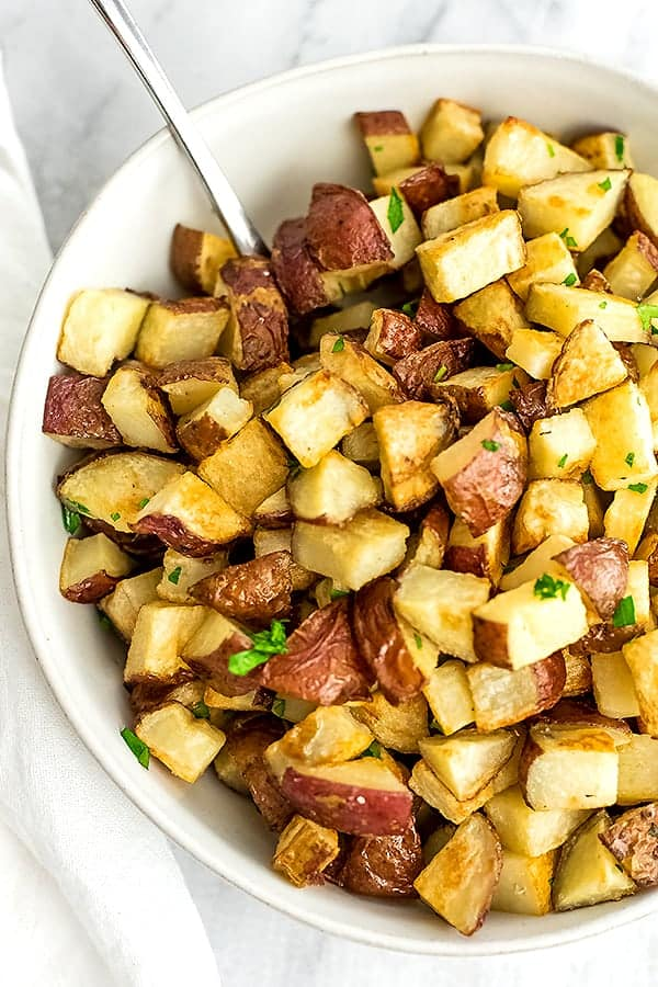 White bowl filled with roasted potatoes.