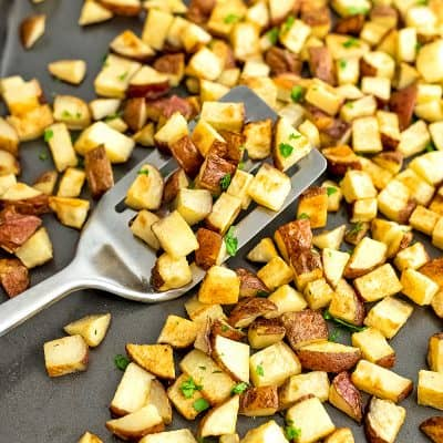 Roasted potatoes on a baking sheet with a silver spatula.
