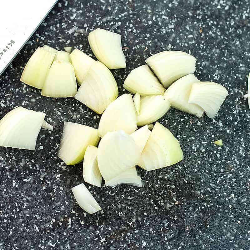 Chopped white onion on a cutting board.