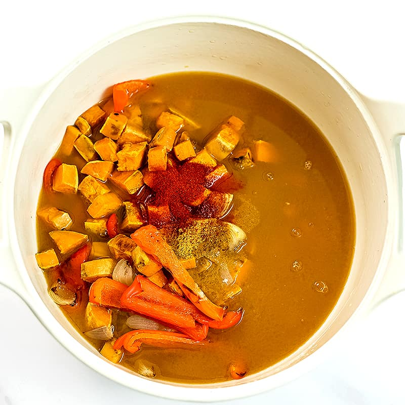 Roasted vegetables, vegetable broth and spices in a large pot before blending.