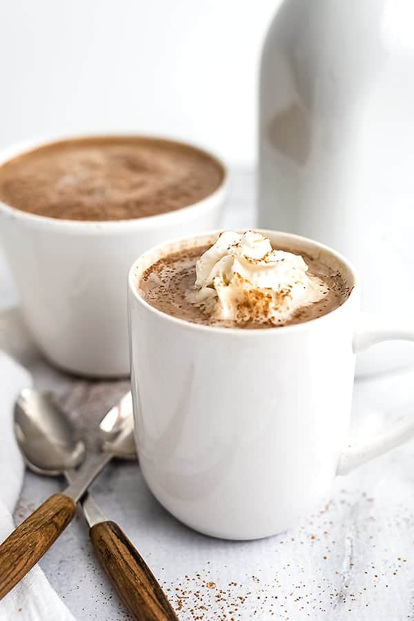 White mug filled with protein hot chocolate with whipped cream.