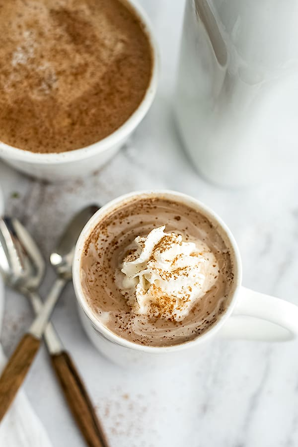 Mug full of protein hot chocolate with spoons to the left.