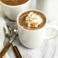 Protein hot chocolate topped with whipped cream in a white mug.
