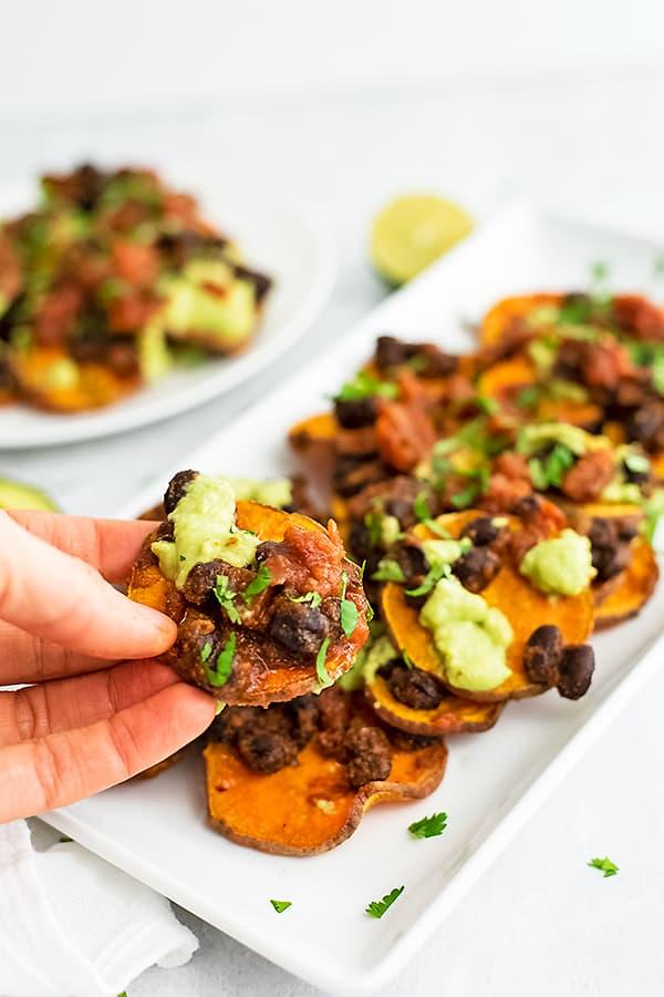 Hand holding a single sweet potato black bean nacho.