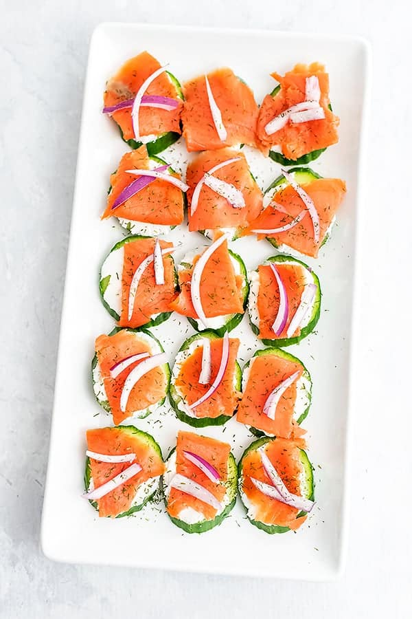 White rectangle plate filled with smoked salmon cucumber bites.
