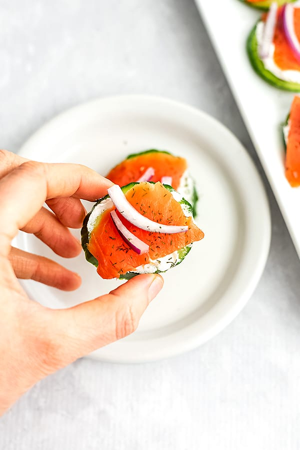 Hand holding a smoked salmon cucumber bite.