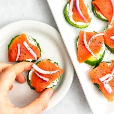 Smoked salmon cucumber bite on a small white plate.