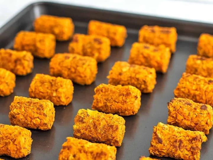 Sweet potato tots in rows on a grey baking sheet