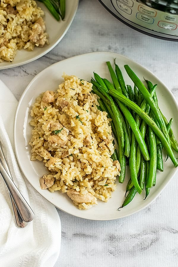 White plate filled with instant pot chicken and rice and green beans.