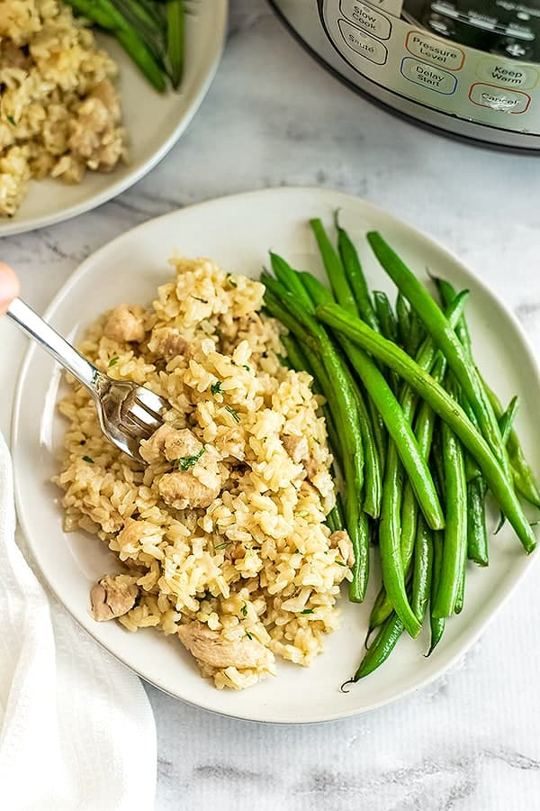 Instant Pot Brown rice and chicken thighs on a plate with green beans.