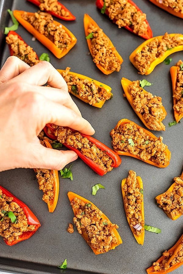 Hand grabbing a mini pepper nacho from the tray.