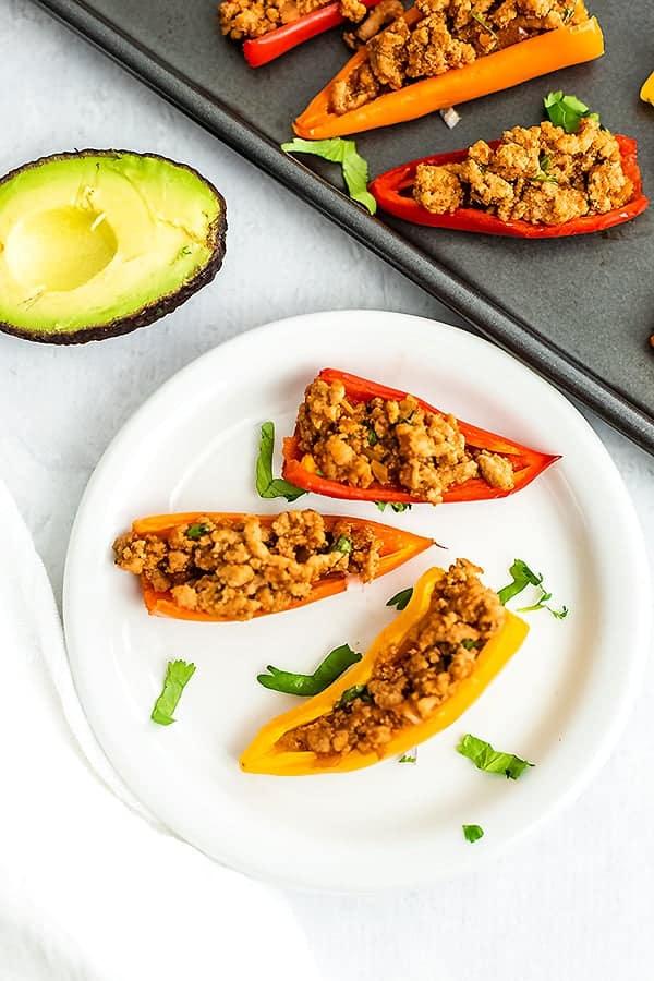 White plate with mini pepper nachos. Avocado in background.