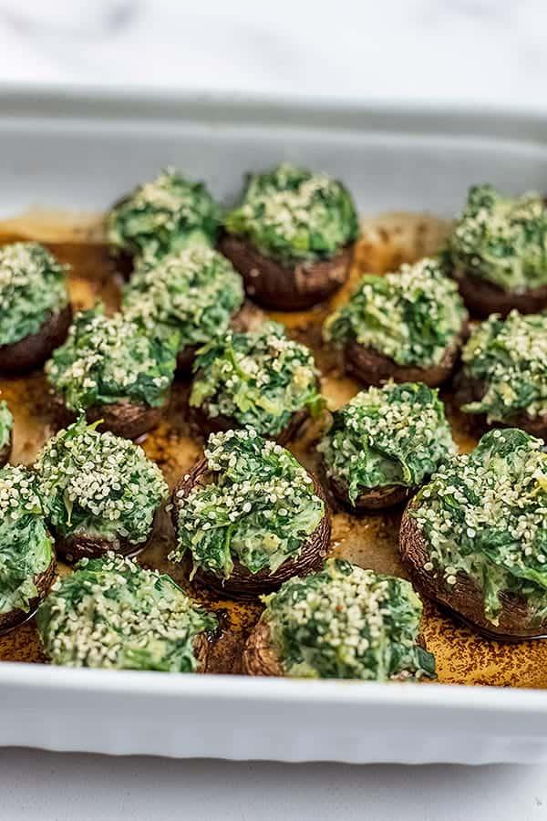 White baking dish filled with vegan spinach artichoke stuffed mushrooms.