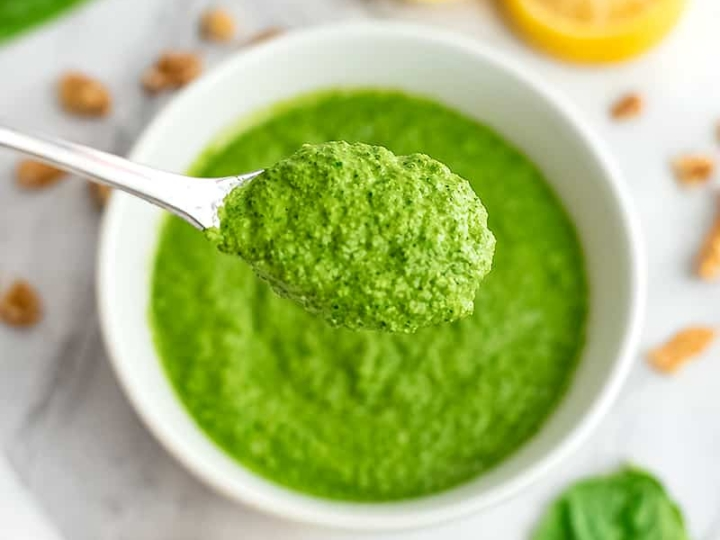 Large spoonful of spinach walnut pesto over a bowl.
