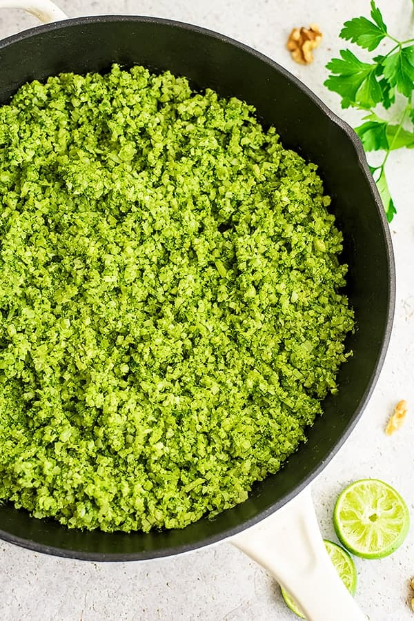 Cast iron skillet filled with green cauliflower rice.