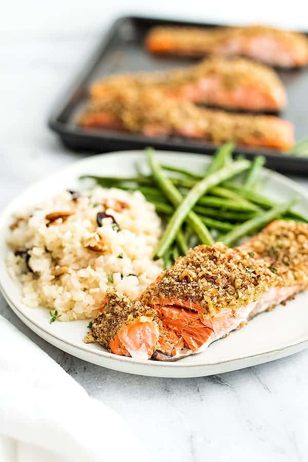 White plate with pecan crusted salmon, green beans and cauliflower rice.
