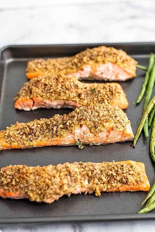 4 filets of pecan crusted salmon on a baking sheet.