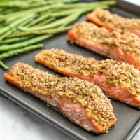 Baking sheet with 4 pieces of pecan salmon and green beans.