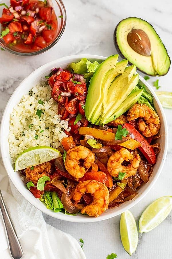 Shrimp fajita bowls filled with avocado, cauliflower rice and salsa.