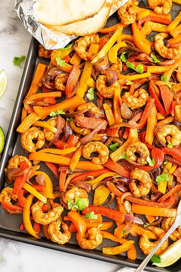 Shrimp fajitas cooked on a sheet pan with tortillas in the corner.