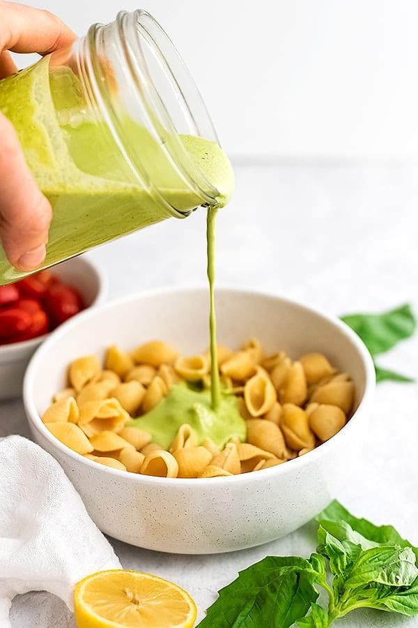 Jar pouring tahini pesto over pasta.