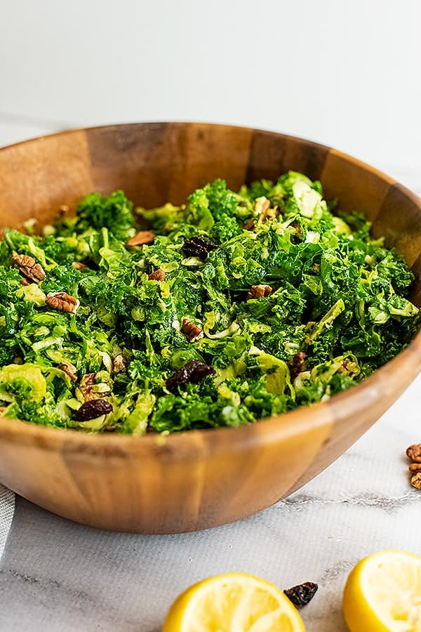 Wooden salad bowl filled with kale brussel sprouts salad.