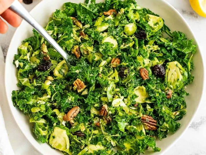 Fork in a bowl of kale brussel sprouts salad.