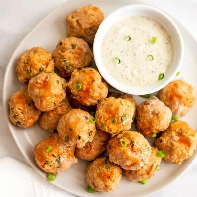 Buffalo Turkey Meatballs on a white plate with a side of ranch.